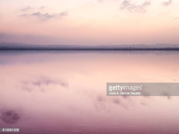 Sunset on a salt lake with its calm waters and pink