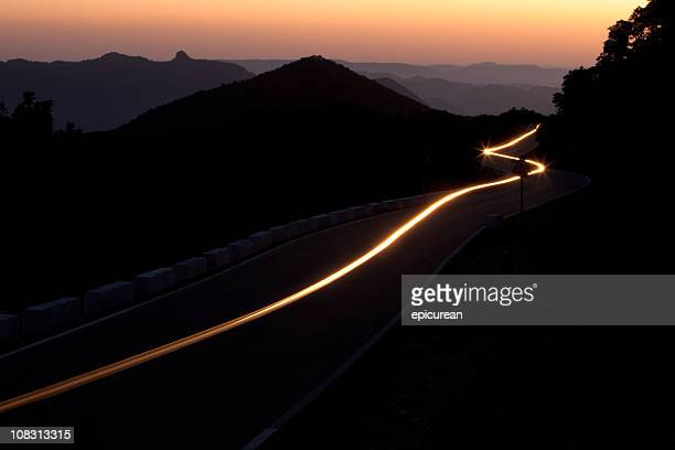 Sunset on a winding highway through the mountains