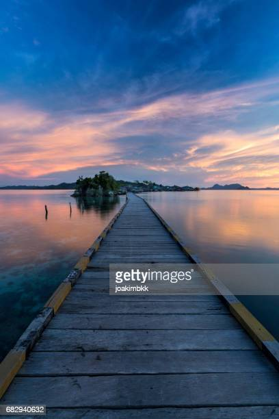 Sunset on a wooden jetty in Sulawesi island in Indonesia