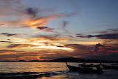 Sky landscape, sunset on Andaman sea with silhouette of  rowboats, Ao Nang beach, Thailand.