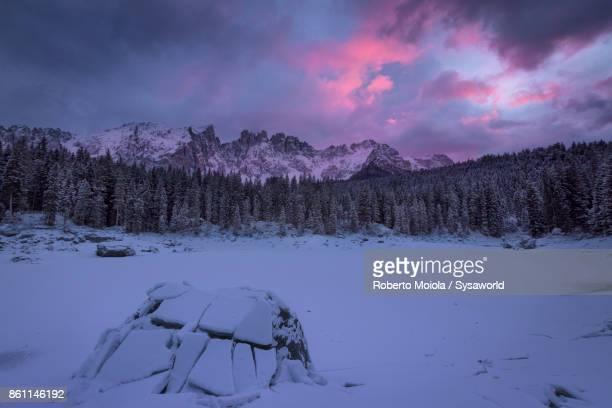 Sunset on frozen Lake Carezza, South Tyrol, Italy