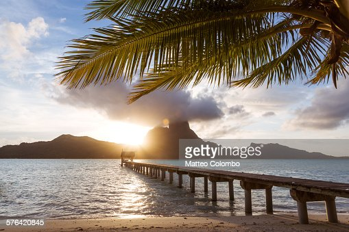 Sunset on jetty and palm tree, in Bora Bora lagoon