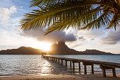 Sunset on jetty and palm tree, in Bora Bora lagoon