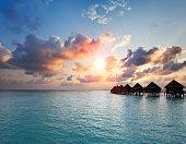 Sunset on Maldives island, water villas, bungalow on sea