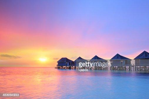Sunset on Maldives island, water villas resort : Stock Photo