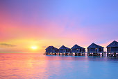 Sunset on Maldives island, water villas resort