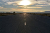 Sunset, flat valley, two people walking on a wide straight empty asphalt road towards the sun at the horizon
