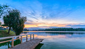 Sunset on the shores of Xuan Huong Lake with dramatic sky makes the scenery more romantic, attracting tourists to visit in Dalat, Vietnam.