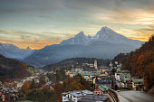 """Dusk settles over """"Watzmann"""", the tallest mountain located fully within German borders. A winding road leads from the lower right down into the historic town of Berchtesgaden below."""
