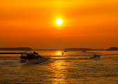Orange skies over a Dorset harbour with various boats silhouetted on the sea