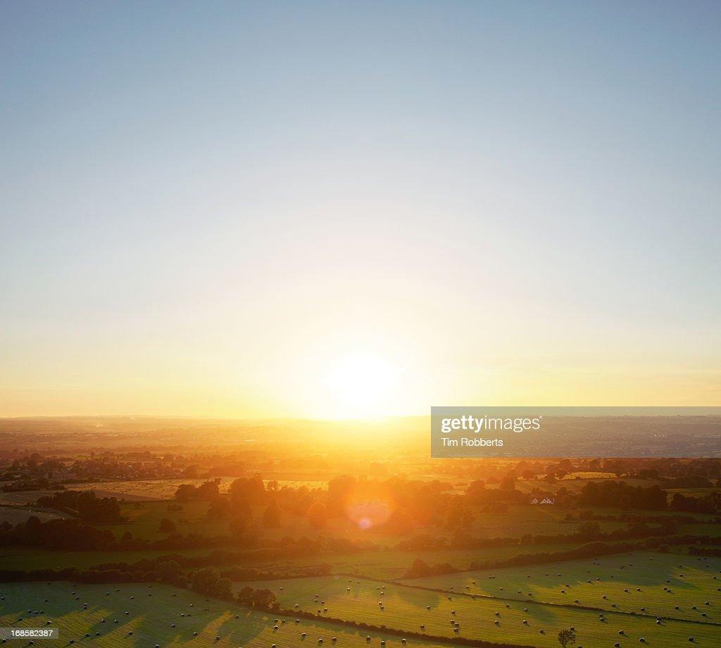 Sunset over green fields landscape.