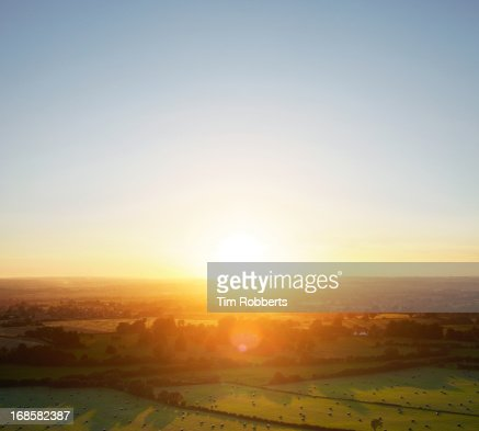 Sunset over green fields landscape.
