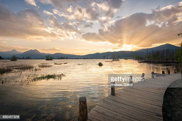 Sunset over mountains, lake and boardwalk in Lijiang, Yunnan, China, Asia