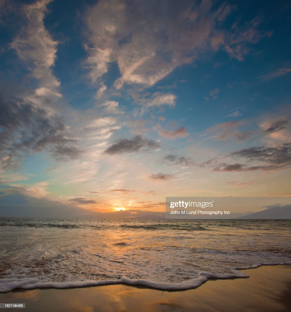 Sunset over ocean waves at beach : Stock Photo