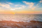 Sunset over rock beach skyline, natural landscape background