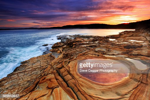 Sunset over rock formation and sea