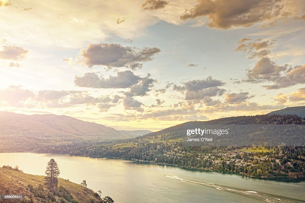 sunset over rolling hills and lake with water ski