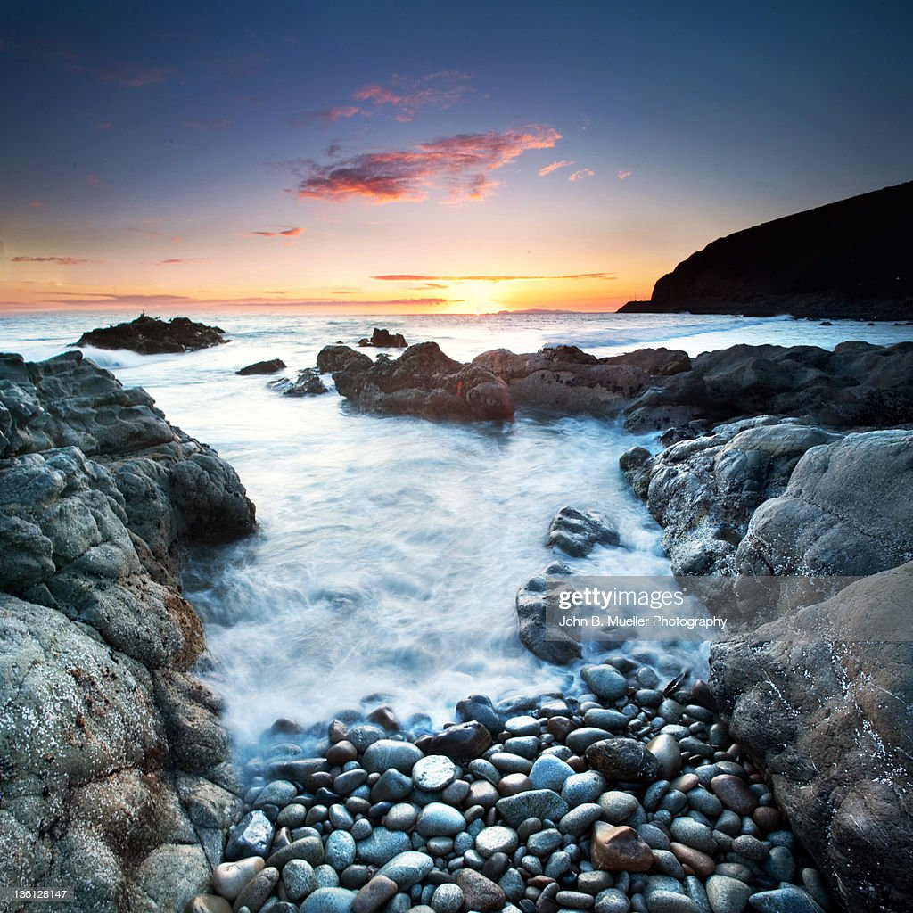 Sunset over sea with pebbles in background