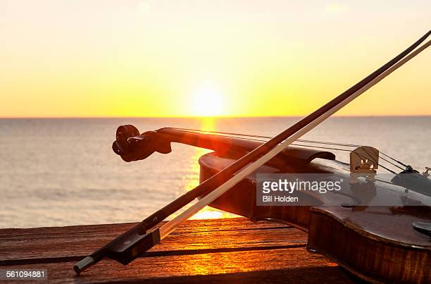 Sunset over sea with violin and bow on bench