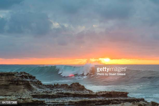 Sunset over waves breaking on rocky shore