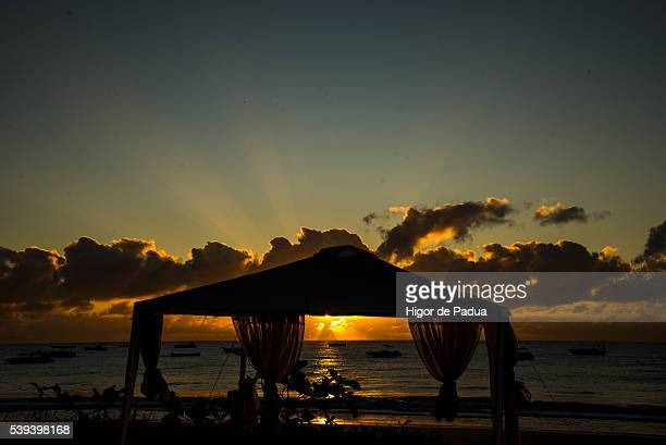 A sunset overlooking the beach and the silhouette of a large beach tent with decorative cloths