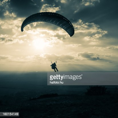 Sunset paragliding with clouds