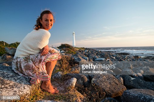 Sunset portrait of young woman with lighthouse in background : Foto de stock