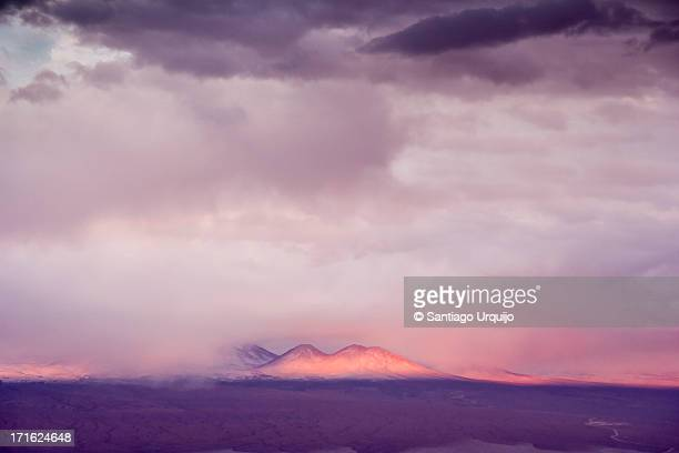 Sunset rays hit Cordillera Domeyko during a storm