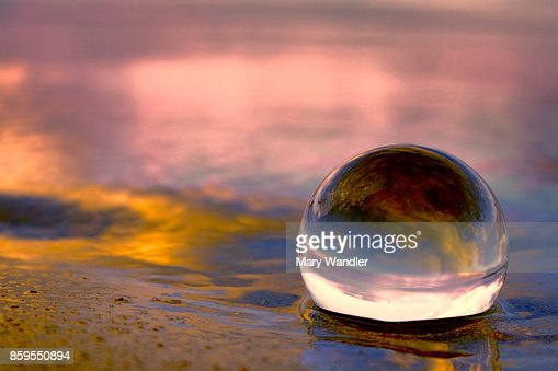 Sunset reflecting in a glass ball on the beach : Stock Photo