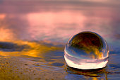 Summer sunset displayed through a transparant glass ball on the beach sand