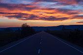 Straight road with  horizon with beautiful sunset sky at dusk -Recta en carretera  y horizonte con bonito cielo de atardecer al anochecer