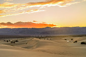 A colorful Spring sunset at Mesquite Flat Sand Dunes, with Stovepipe Wells village seen at base of Panamint Range. Death Valley National Park, California, USA.