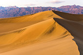 A Spring sunset view of rolling sand dunes standing tall at front of rugged mountains of Amargosa Range. Mesquite Flat Sand Dunes of Death Valley National Park, California, USA.