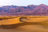 Spring sunset view of smooth and curvy sand dunes stretching out at base of rugged purple mountains of Amargosa Range. Mesquite Flat Sand Dunes of Death Valley National Park, CA, USA.