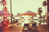 Sunset scene by the pool with umbrella and deck chair.Vintage filter effect.