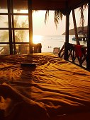 A view of sunset over the sea from the bedroom inside a beach hut on Pulau Perhentian Besar, Malaysia