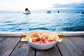 Prawns on ice on a jetty with cold beer, boats in distance