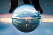 Sunset seascape captured in clear glass ball held in fingers