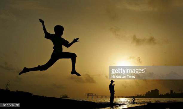 Sunset Seashore Arabian Sea While a life guard keeps a close watch on a cyclist near the water's edge a child does a Krrish act at Mahim beach on...