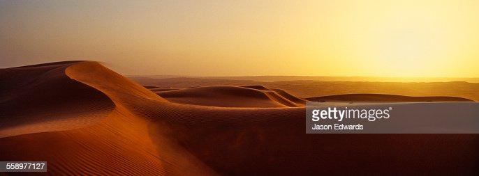 Sunset shines on sand dunes in the desert.