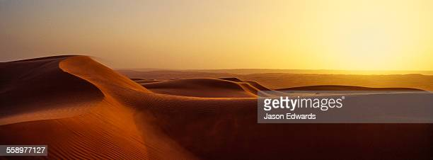 Sunset shines on sand dunes in the desert.