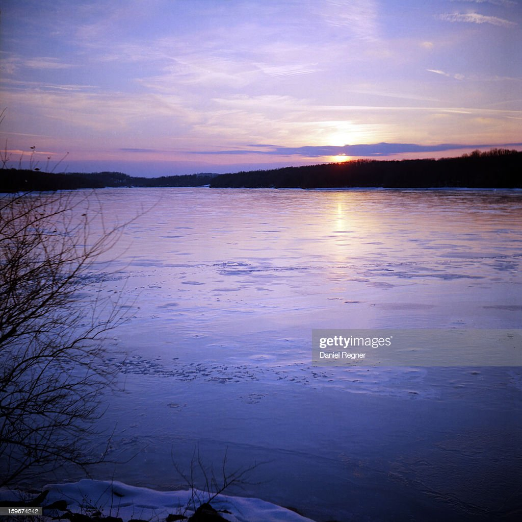 CONTENT] A sunset shot over a frozen cold lake Marburg, in Codorus State Park in Pennsylvania. The water is purple and red tinted from the light of magic hour and the sunset. Beautiful natural landscape, serene in the winter air.