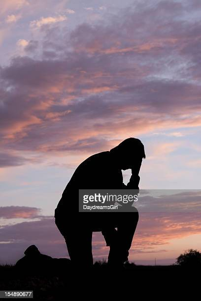 Sunset Silhouette of Man Kneeling and Head Bowed