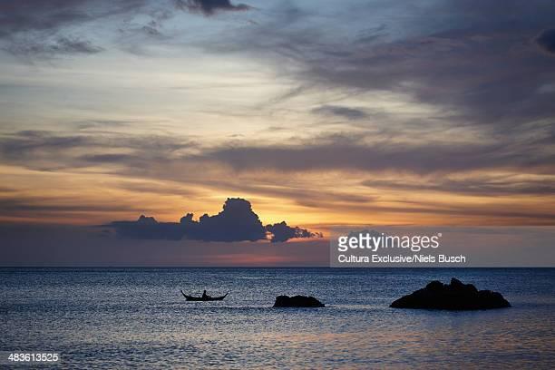Sunset silhouette of sea rocks and boat, Koh Lanta, Thailand