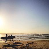 Sunset silhouette of surfers walking along beach