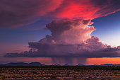 Sunset storm clouds reflect colorful light as a thunderstorm builds on the horizon.