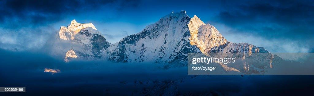 Sunset summits snowy peaks panorama illuminated through clouds Himalayas Nepal