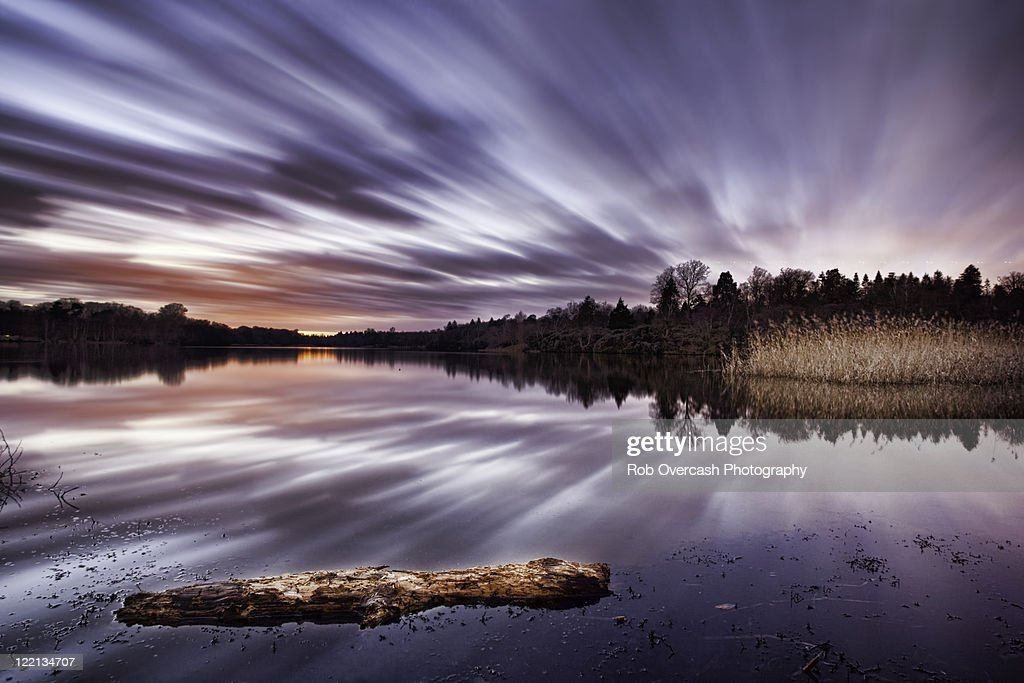 Sunset with dramatic clouds over lake : Stock Photo