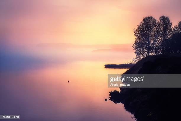 Sunset with fog over calm waters.