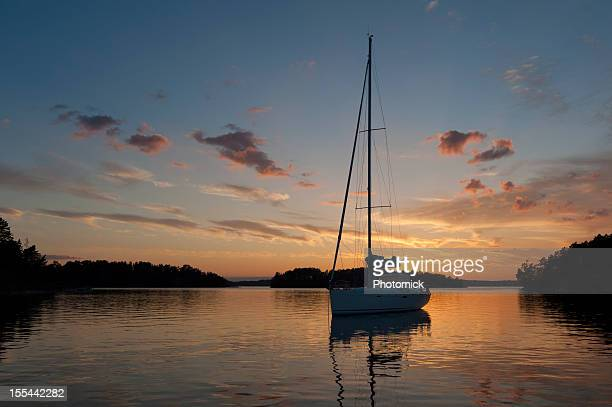 Segelboot bei Sonnenuntergang mit Anker im Archipel